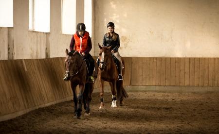 Indoor shot of two woman jockeys doing training in riding hall photo