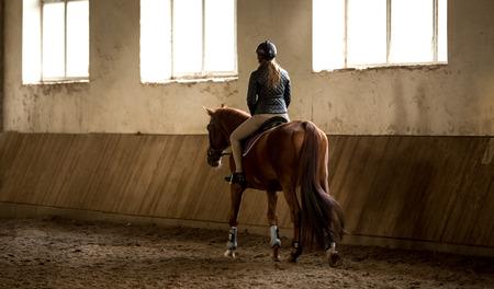 Foto uit achterkant van de vrouw doen paardrijden in de manege