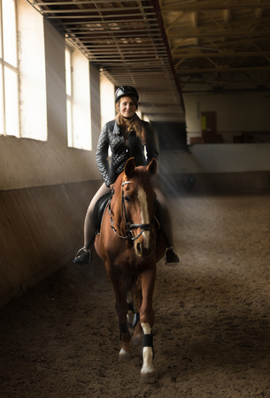 Indoor photo of young woman jockey riding horse on manege photo