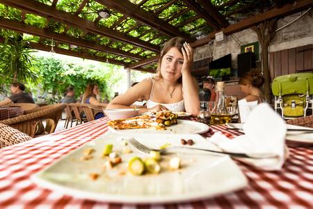 Primer retrato de mujer comer en exceso mirando los platos vacíos en la mesa en el restaurante Foto de archivo