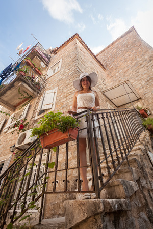 Beautiful young woman standing on balcony at old stone house photo