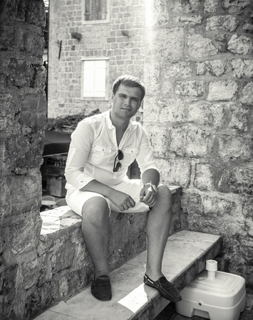 Black and white photo of handsome man sitting on old street at sunny day