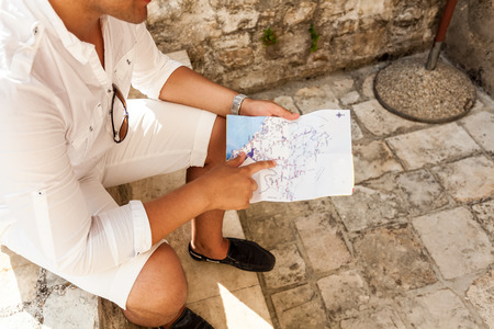 Closeup photo of young man sitting on street and pointing at map photo