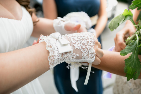 lace gloves: Closeup shot of beautiful bride wearing white lace gloves