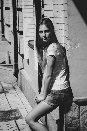 Monochrome portrait of young woman leaning against brick wall at sunny day photo