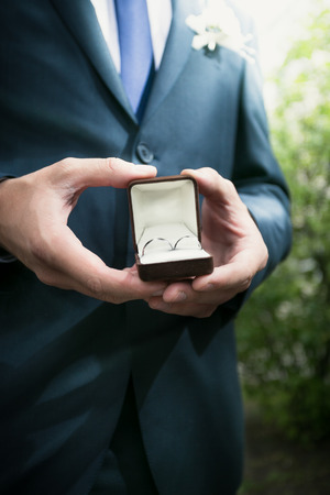 Closeup view elegant groom holding open box with wedding rings photo