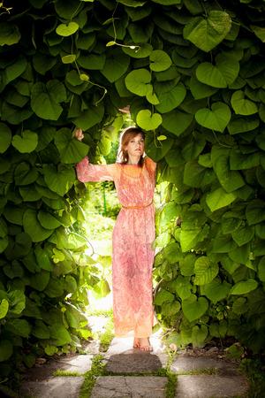 femme romantique: Belle femme romantique posant au arche florale au jardin