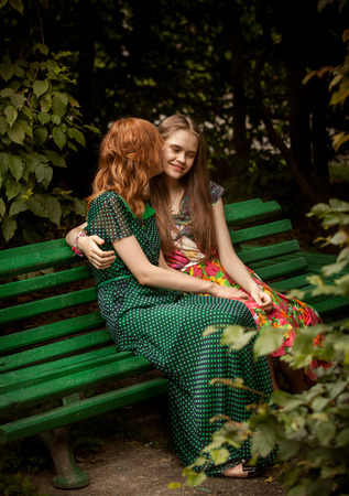 beautiful redhead: Beautiful redhead woman kissing brunette girl on bench at park