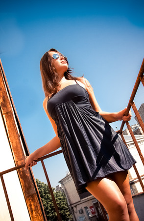 tanned latin girl in short dress leaning against metal railings Stock Photo