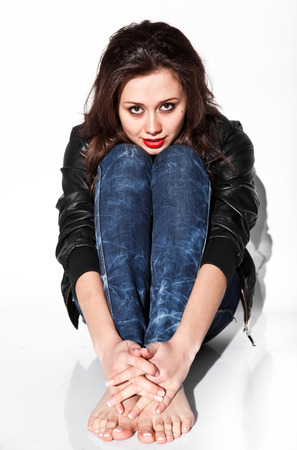 leather coat: Closeup portrait of sad brunette woman in leather coat and jeans sitting on floor at studio