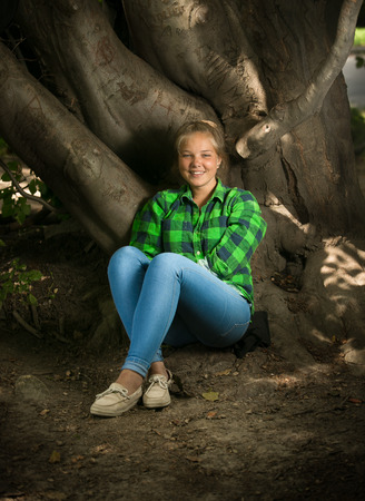 Beautiful blonde girl in shirt and jeans sitting under big tree photo