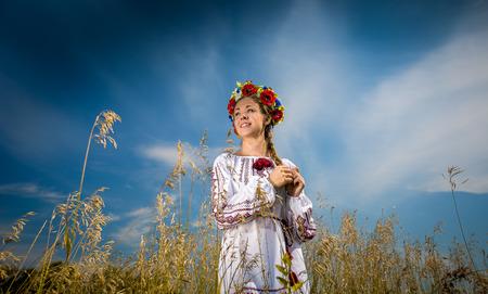 Portrait of beautiful ukrainian girl with braid posing at field photo