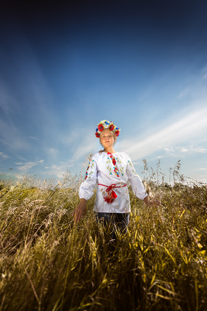 Beautiful young girl in ukrainian clothes walking at wheat field photo