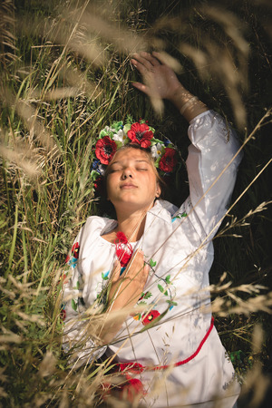 hymn: Closeup portrait of girl in ukrainian clothes lying in high grass Stock Photo