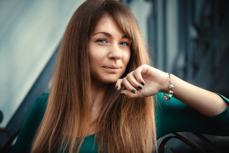 Closeup toned portrait of woman with long hair posing on street and holding hand near lips photo