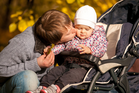 Closeup portrait of father kissing daughter sitting in buggy at park photo