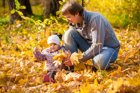Outdoor photo of young father playing with small daughter at park photo