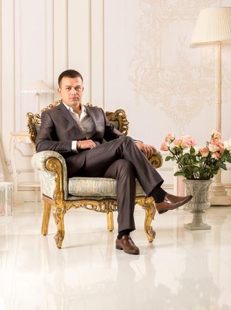 Knappe elegante man in het zwart pak zitten in een luxe stoel klassiek interieur Stockfoto