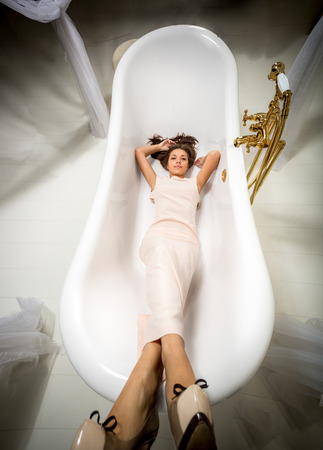 clothed: Elegant woman in long dress lying in luxurious bath