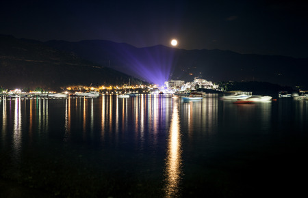 Beautiful landscape of moon shining over seaside city at dark night photo