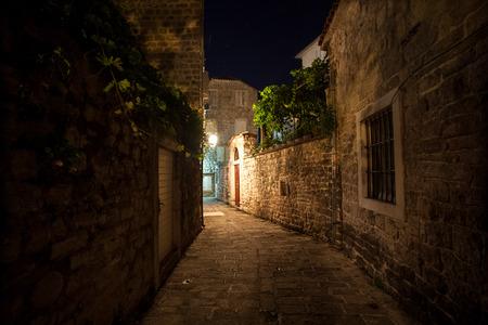 Long old narrow street lit by gas lanterns at night photo