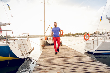 Handsome man walking on pier against yachts at sunny day photo