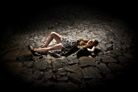 ancient sexy: Sexy young blond woman lying on ancient stone road at night Stock Photo