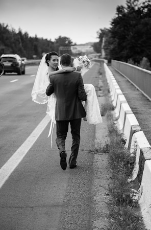 Black and white photo of strong groom walking on road and carrying bride on hands photo