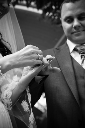 Black and white closeup shot of bride putting wedding ring on grooms hand photo