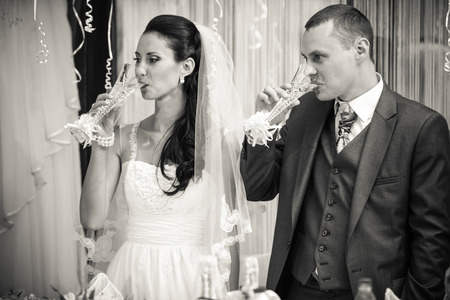 gulp: Black and white photo of bride and groom drinking champagne after toast