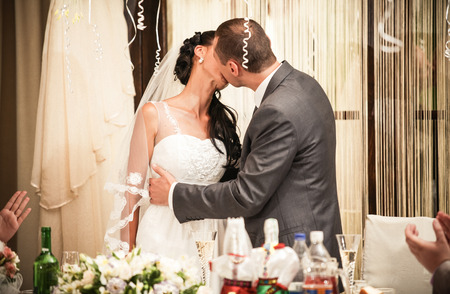passionately: Young bride and groom kissing passionately behind table at banquet Stock Photo