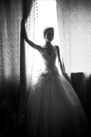 window shade: Black and white silhouette photo of bride holding shade at window
