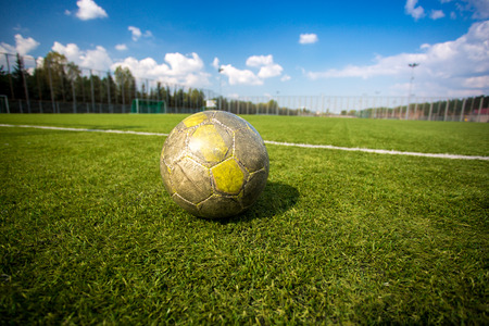 Old shabby soccer ball lying on artificial grass field photo