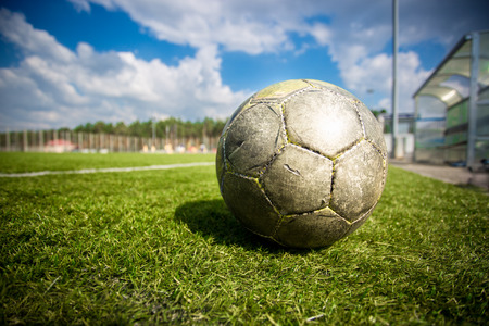 Closeup shot of old soccer ball on grass field at sunny day photo
