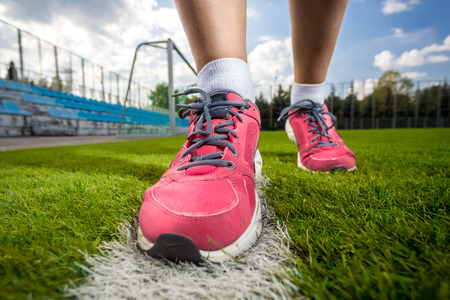Closeup photo of pink female sneakers on soccer grass field photo