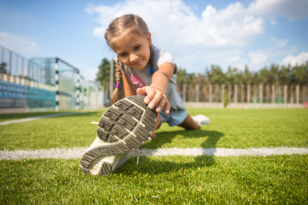 children and sport: Cute young girl stretching on grass before running