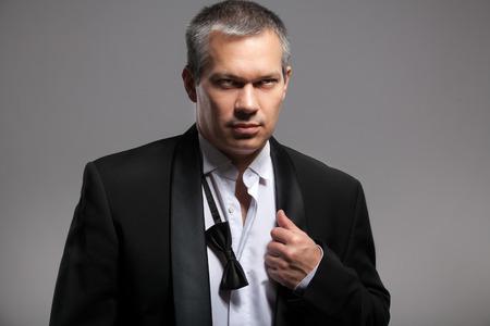 untied: Primer retrato de hombre atractivo en juego con la pajarita desatada