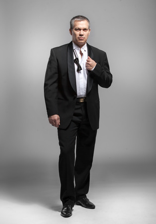 untied: Full length portrait of elegant man in black suit with untied bow tie