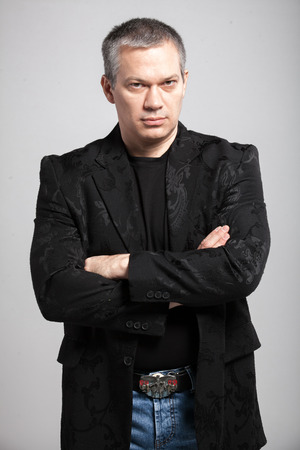 Closeup portrait of adult man in black jacket holding hands crossed