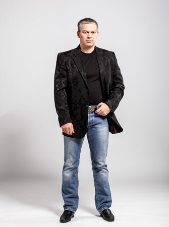 enticement: Full length studio portrait of adult man in jeans and black jacket