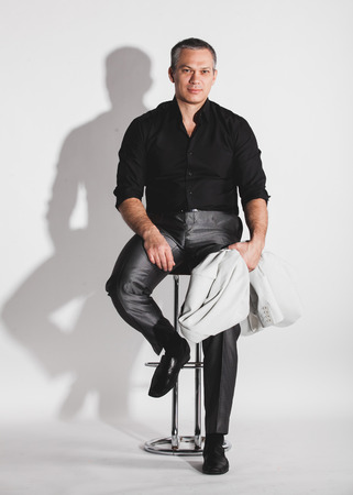 bar chair: Handsome sexy man in black shirt sitting on bar chair Stock Photo