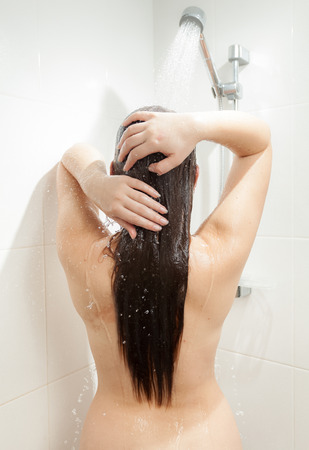 Closeup photo from back of brunette woman washing head photo