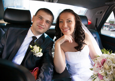 Closeup portrait of newly married couple sitting on back seat of car and looking at camera