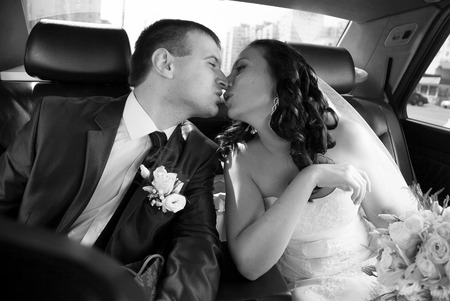 Black and white portrait of bride and groom kissing on backseat of car photo