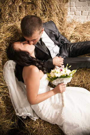 Closeup portrait of beautiful bride and groom kissing on stack of hay photo