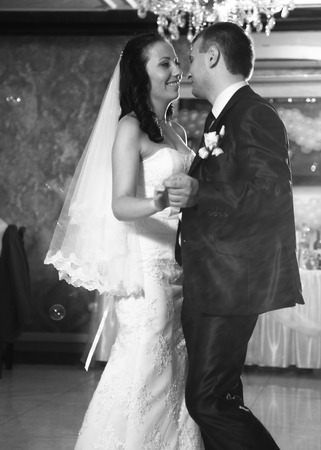 Black and white photo of happy newly married couple dancing at restaurant photo