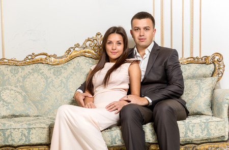luxurious sofa: Portrait of couple in love hugging on luxurious sofa