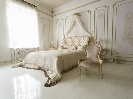 Beautiful interior of classic white bedroom with big bed and chair