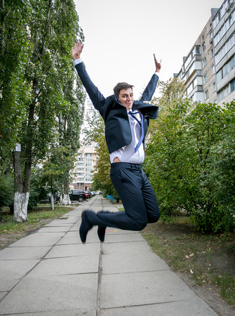 buisinessman: Outdoor shot of excited businessman in suit jumping on street