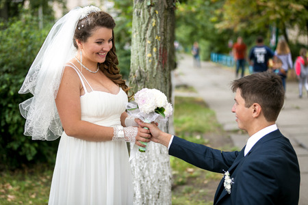 Portrait of handsome groom giving bouquet to smiling bride at park Stock Photo